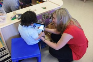 LEND SLP Trainee working with preschool-aged child using an iPad